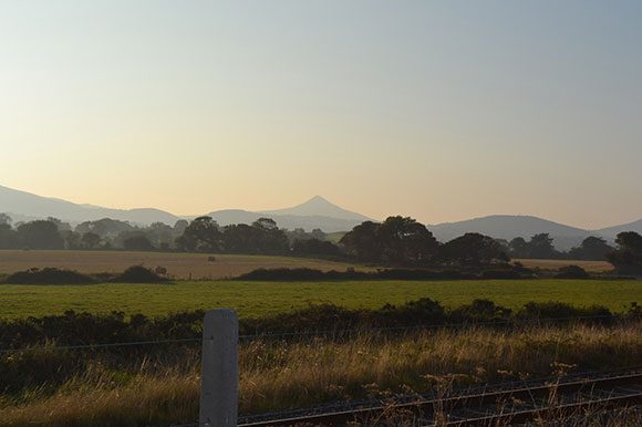The Sugar Loaf, as seen through a summer haze from Kilcoole, Co Wicklow, Ireland